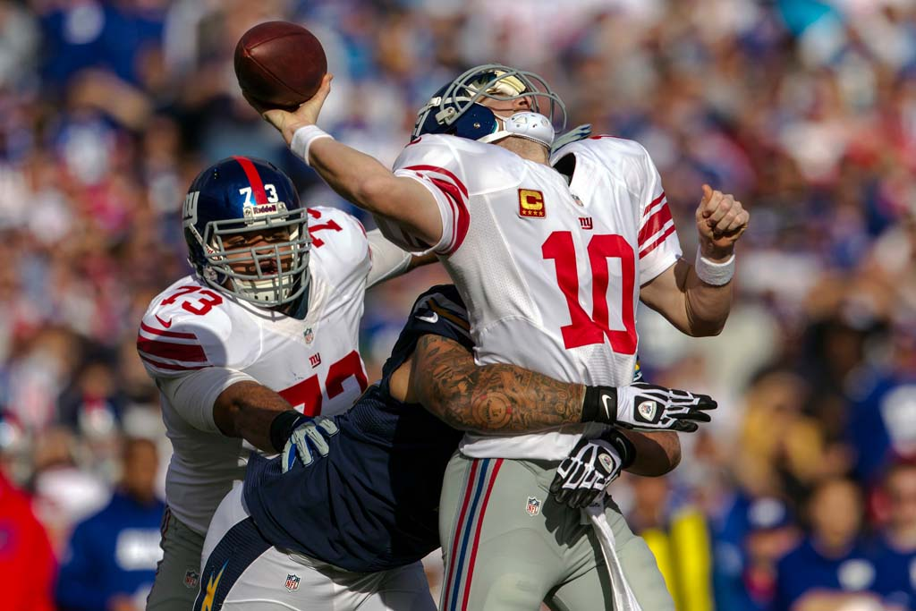 New York Giants quarterback Eli Manning (10) is hit from the blind side by San Diego Chargers defensive end Lawrence Guy (71) in the first quarter at Qualcomm Stadium.