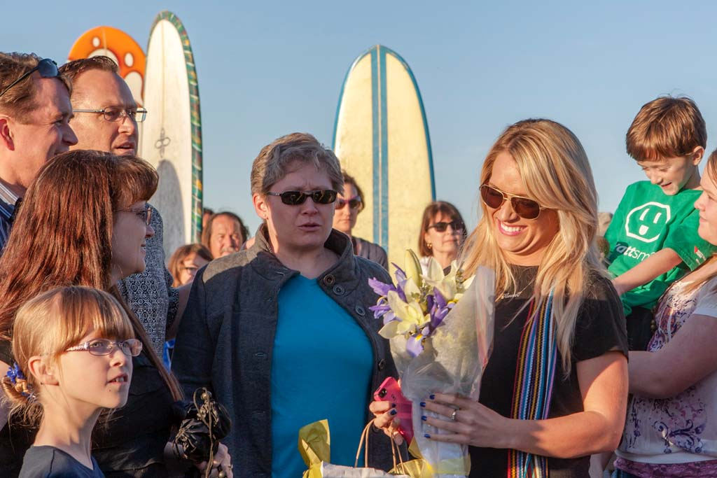 Hannah Nancarrow, right, accepts flowers in honor of her father, longtime San Diego television journalist Loren Nancarrow during a memorial paddle out and beach gathering held at South Cardiff State Beach. Photo by Bill Reilly