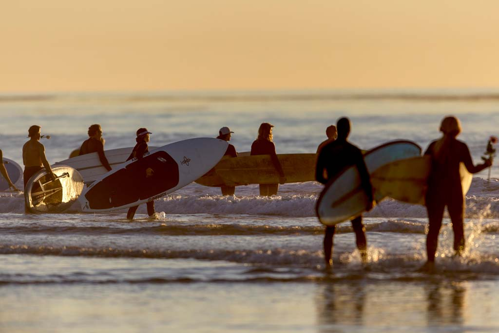 Friends of longtime San Diego television journalist Loren Nancarrow participate in a memorial paddle out and beach gathering at South Cardiff State Beach. Photo by Bill Reilly