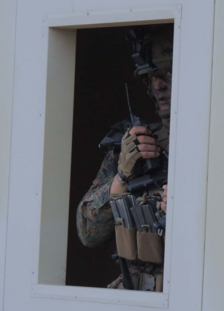 A Marine radios other units with information as other troops dash around outside, clearing buildings, as part of the exercise. Photo by Rachel Stine