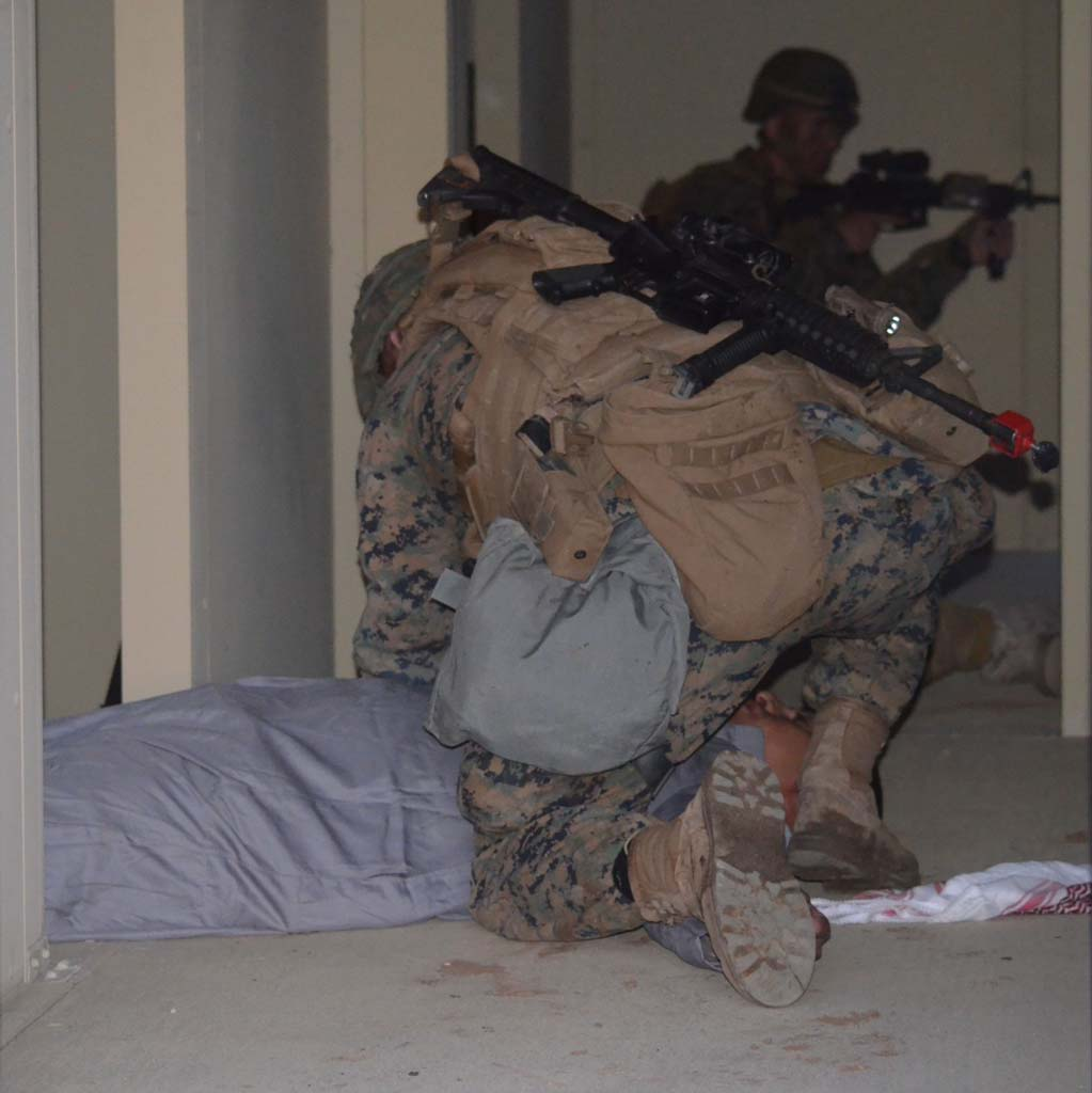 A Marine examines an actor playing an enemy assailant, while other Marines survey the exercise area for other fugitives. Photo by Rachel Stine