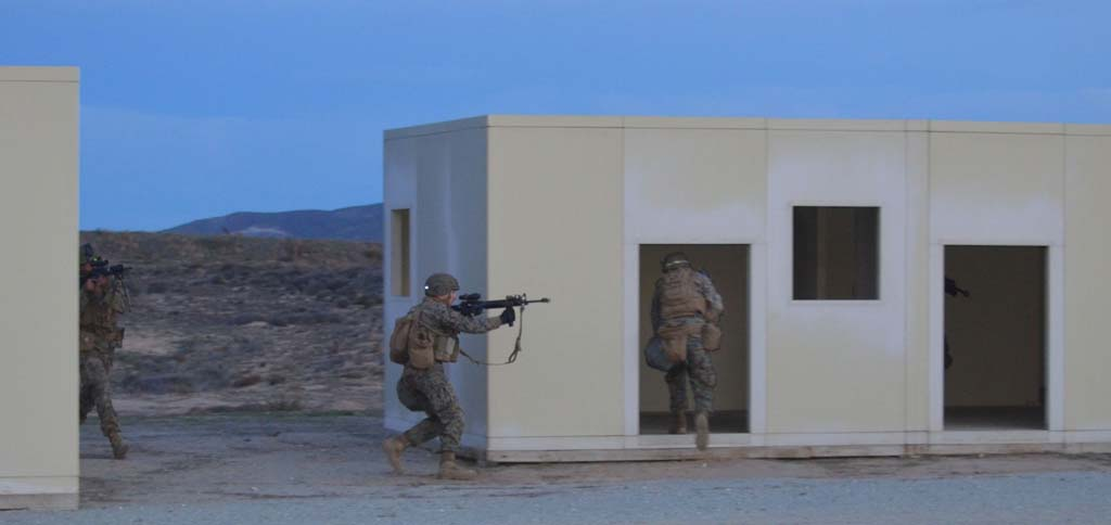 Marines dash into a building in the early morning light during a large-scale training exercise at Camp Pendleton. Photo by Rachel Stine