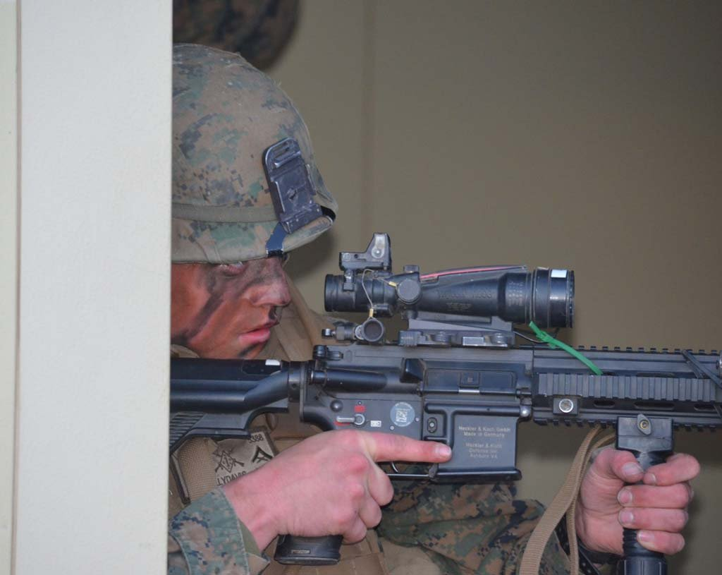 A Marine crouches in the doorway with his weapon at the ready, guarding the entrance to a building with other Marines inside. Photo by Rachel Stine