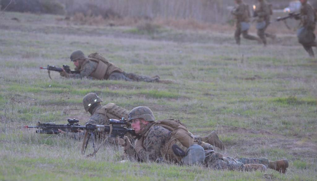 Marines lie low on an embankment, covering others who are running towards a mock enemy town on Camp Pendleton. Photo by Rachel Stine