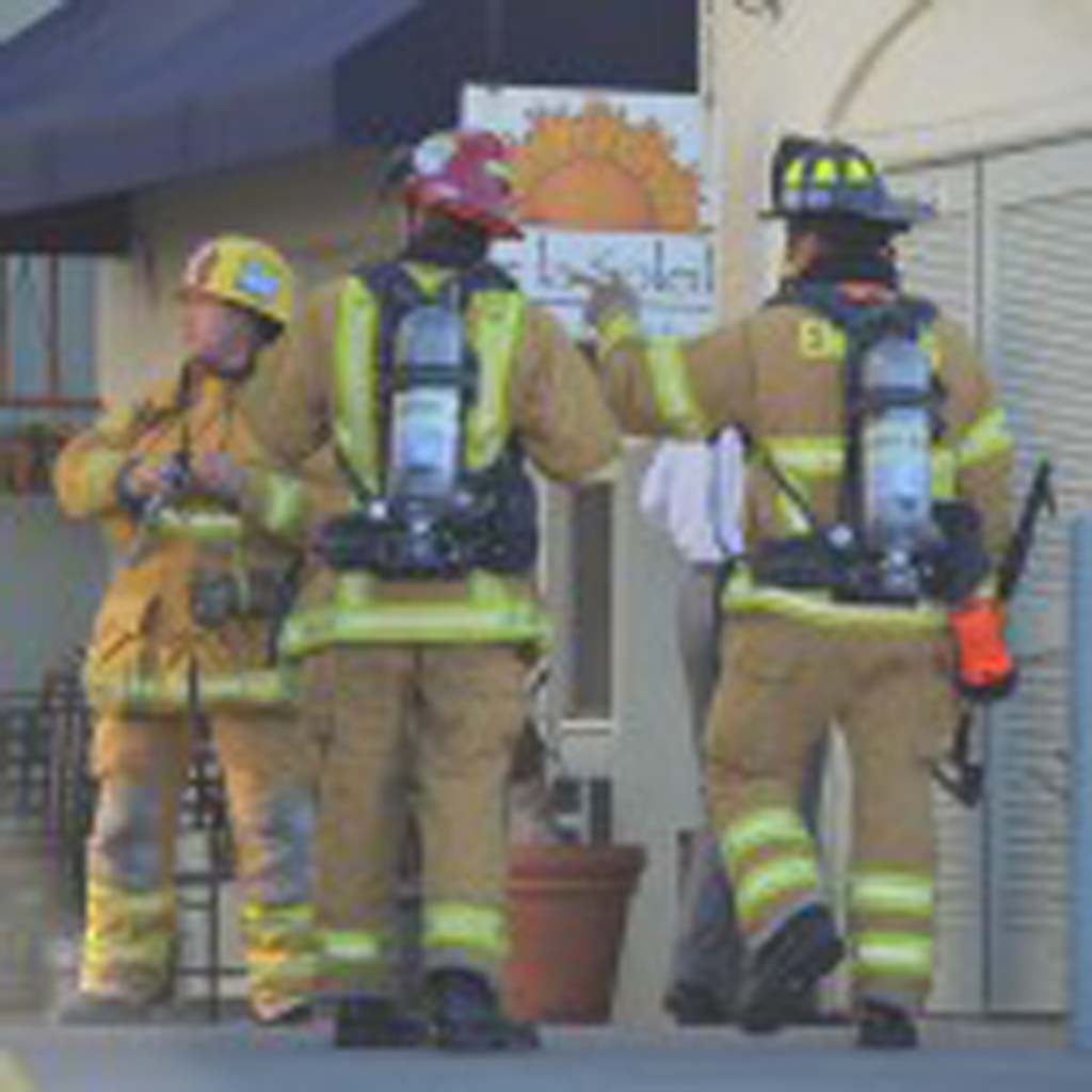 Firefighters from the Encinitas Fire Department examine the Moonlight Shopping Center after a grease fire started in a nearby restaurant. Photo by Tony Cagala