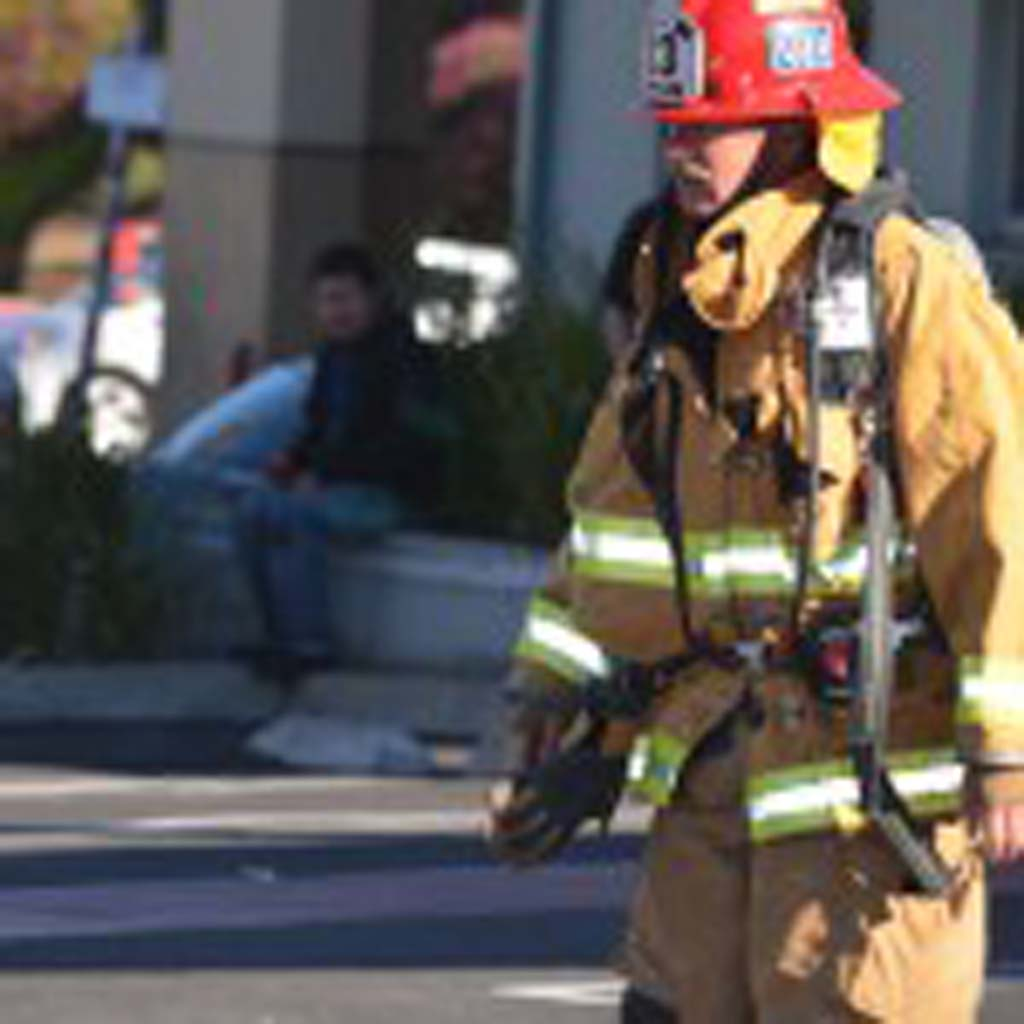 An Encinitas Fire Department captain walks out of the El Callejon restaurant after a grease fire was cleared. Photo by Tony Cagala