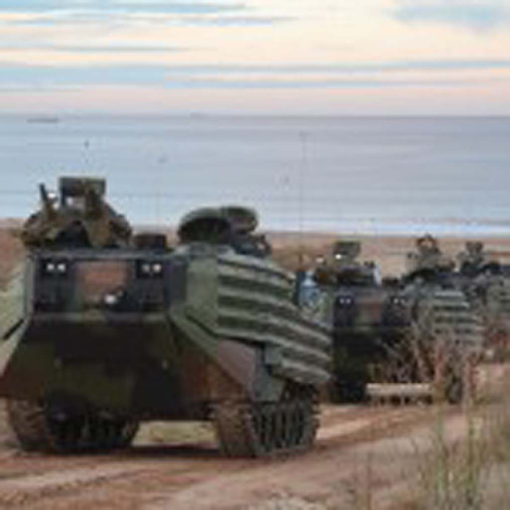 Four of 14 amphibious assault vehicles used in the drill make their way from Red Beach up to a mock-up enemy town shortly after sunrise. Photo by Rachel Stine