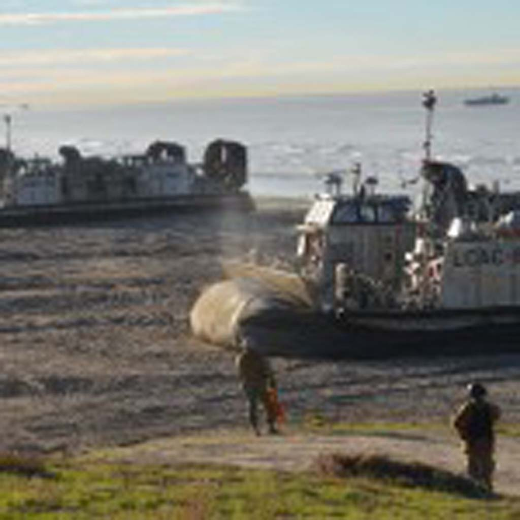 Two U.S. Navy landing craft, air cushion, deflate on the beach before unloading vehicles and equipment. A light armored vehicle sails away from shore in the distance, having landed on the beach about an hour before. Photo by Rachel Stine