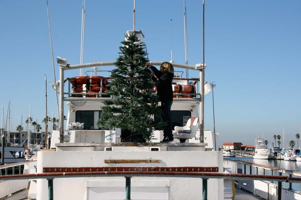 Channing Helgren, 11, decorates the Christmas tree aboard the Electra. The Parade of Lights is set to take sail Dec. 14. Photo by Promise Yee
