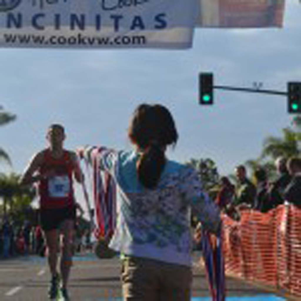 A runner comes through the finish line while a young volunteer waits to award him a medal. Photo by Tony Cagala