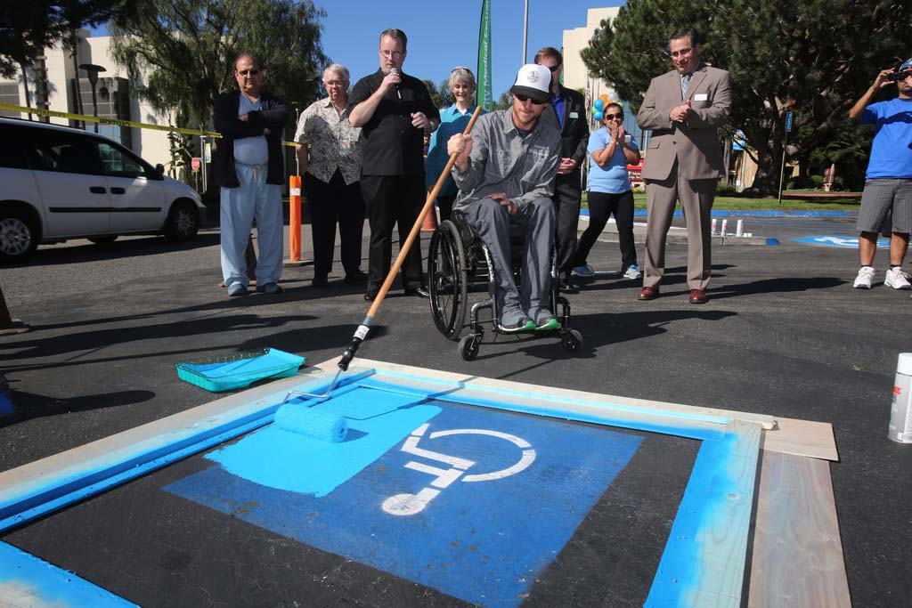 Paraplegic and extreme athlete Jeremy McGhee, of Cardiff, paints over the old accessible parking space to make room for the new accessible icon in Tri City Medical Center's parking lots. Tri-City Medical Center, the first facility in California to partner with the Accessible Icon Project, will replace the icons at its Carlsbad location in the near future.  Courtesy photos