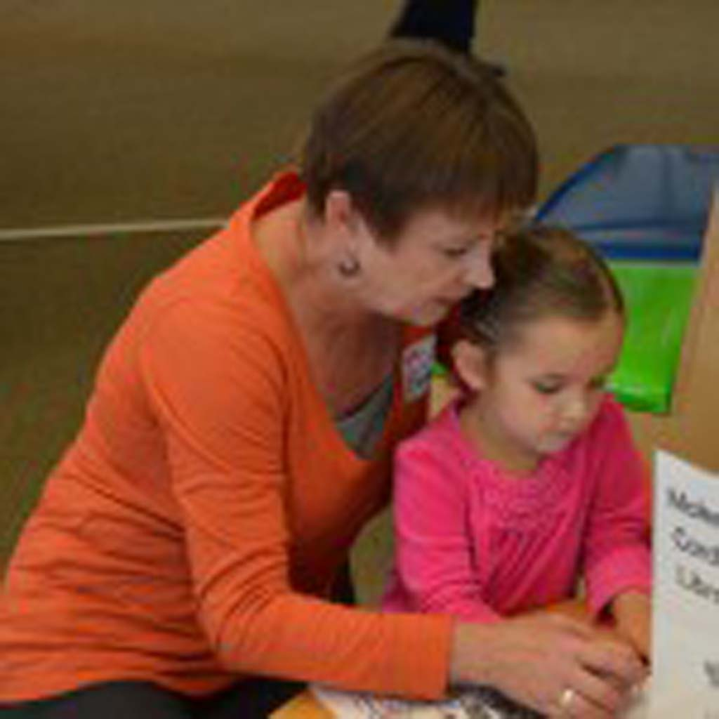 Becky Colvin helps her 4-year-old granddaughter, Josslyn Brownell, draw a birthday card celebrating Cardiff Library's 100th birthday.
