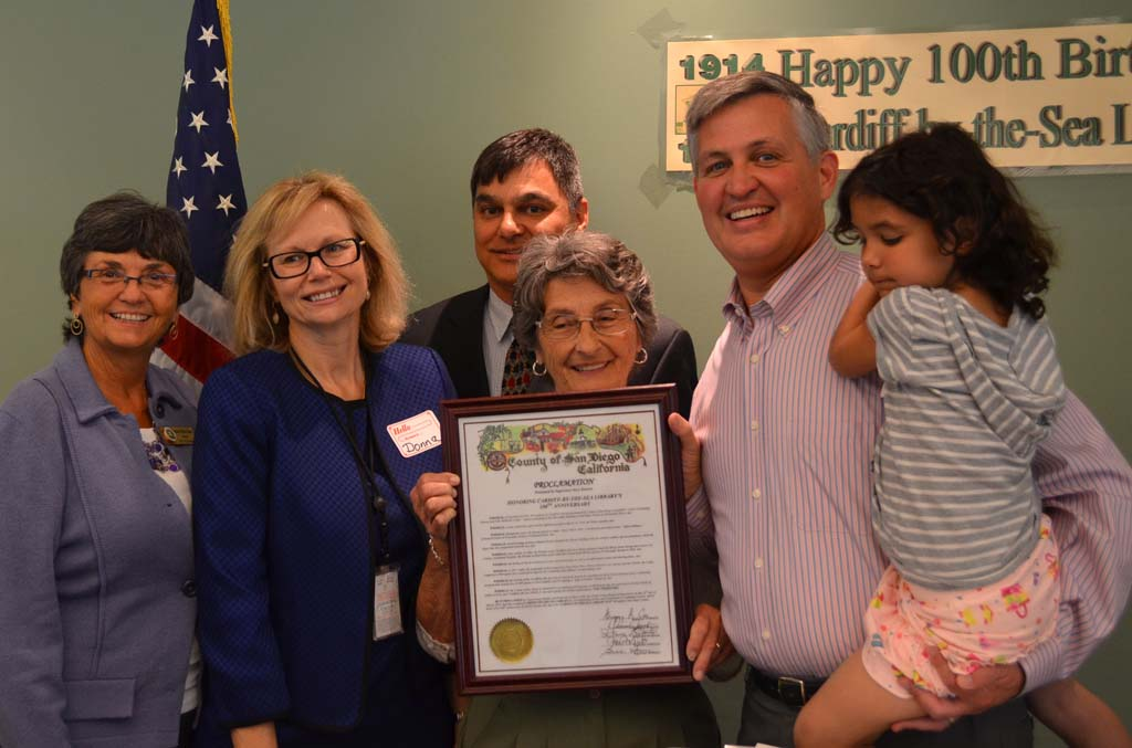 Officials pose with a county proclamation for Cardiff Library. From left to right: Mayor Teresa Barth, San Diego County Library Deputy Director Donna Ohr, Cardiff Library Branch Director Gabriel Aguirre, Friends of Cardiff Library member and past president Irene Kratzer, Supervisor Dave Roberts and his daughter, Natalee.