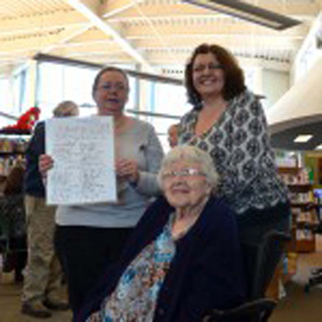 Kathleen Holbrook Stockton poses with daughters Kathleen (right) and Cathy. Cathy holds a copy of the petition that her great-grandparents, along with others, signed in 1913 asking for a library.