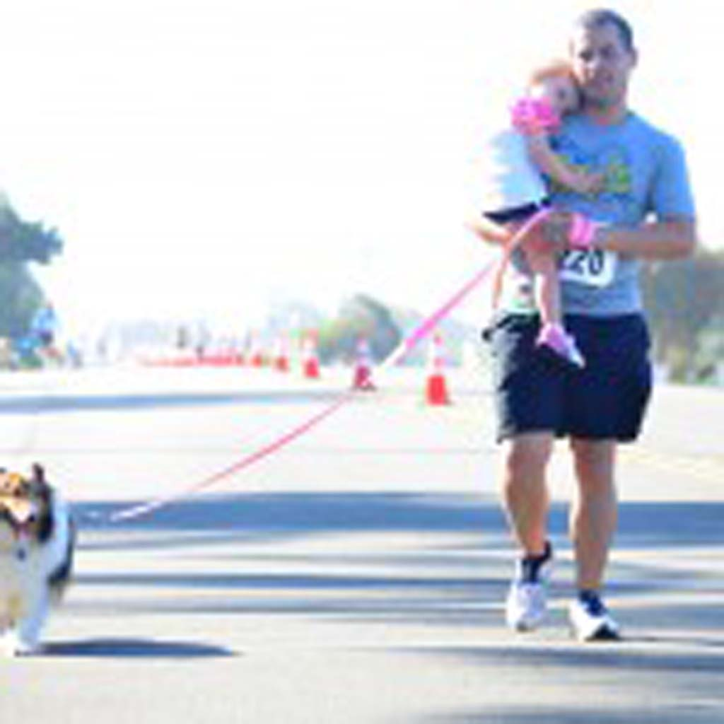 Dewey Smith carries his daughter Natalie towards the finish line of The Encinitas Mile along with their dog Lucky. Photo by Tony Cagala