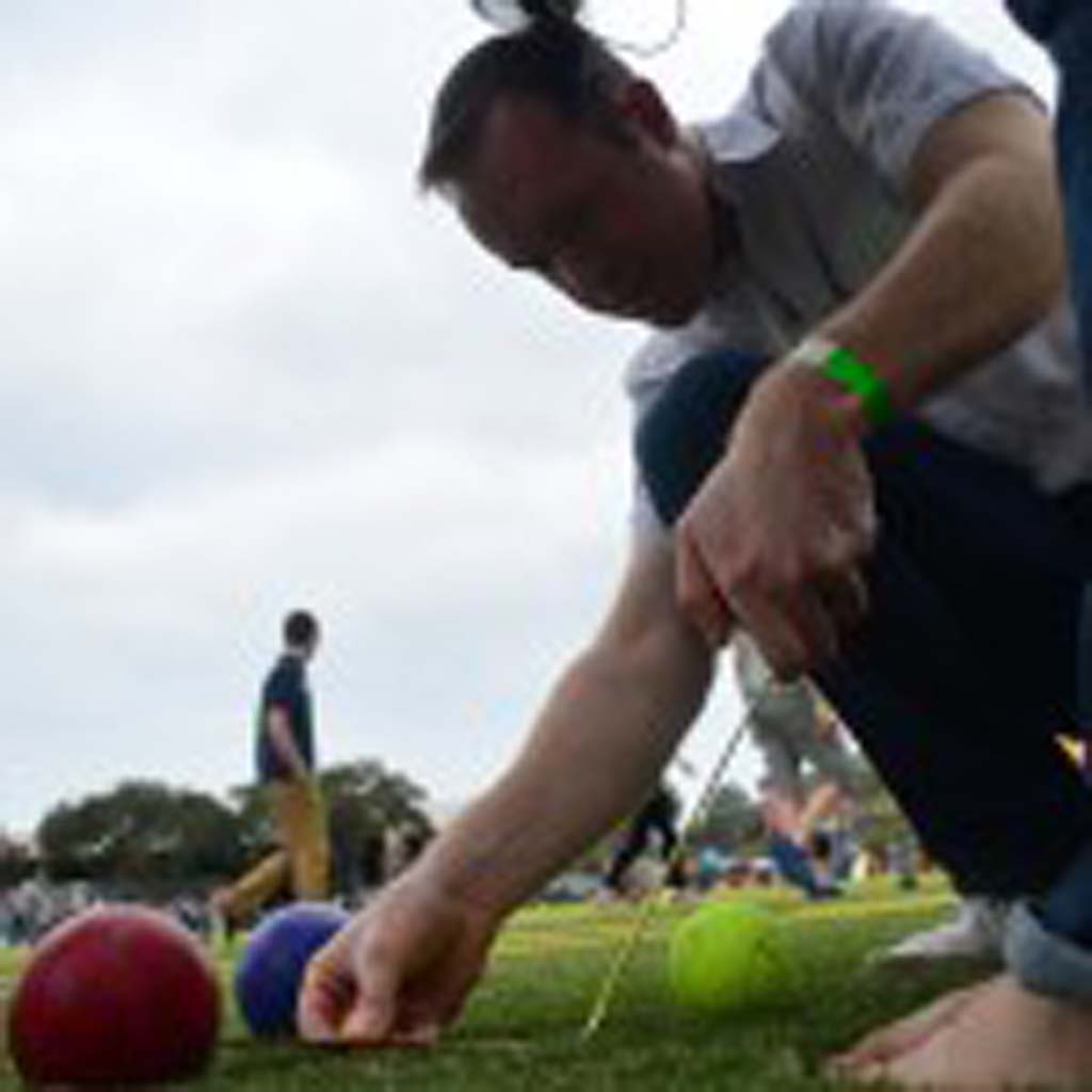 David Paul measures to see which ball is closes to the jack, the smaller ball during a game of Bocce Ball. Photo by Tony Cagala