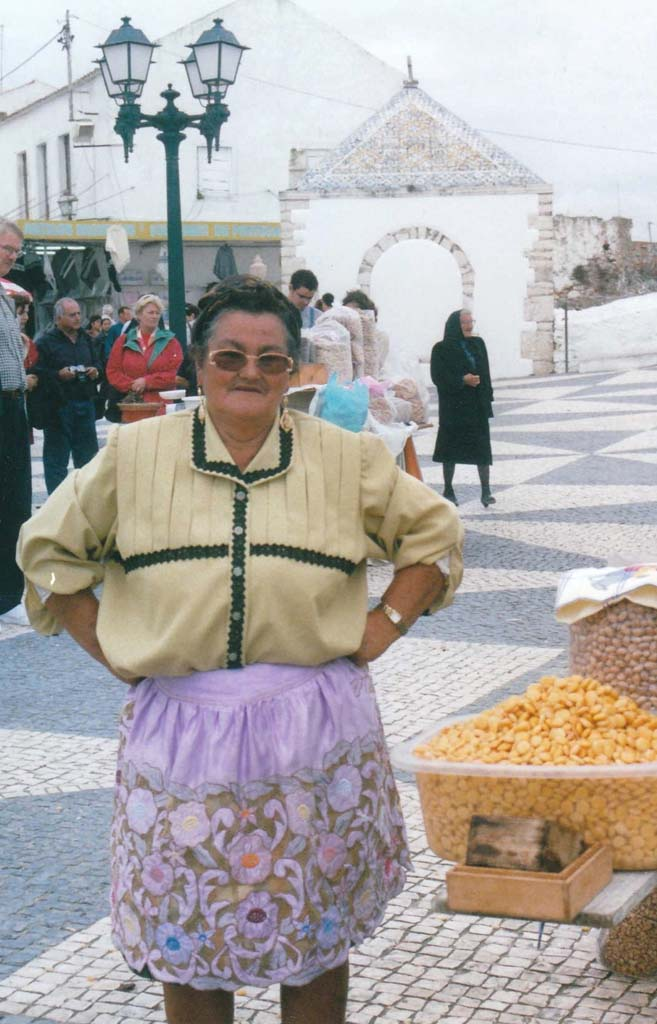 I photographed this colorful and jolly Portuguese street vendor – she grinned and laughed at every potential customer – in October 2002 in the beach town of Nazare. She and many other women who were dressed similarly stood next to their carts loaded with several varieties of roasted nuts in the section of the town built on the top of a cliff. It can be reached only by riding a funicular. Visitors come to Nazare to see the splendid baroque Church of Nossa Senhora da Nazare that houses the statue of Our Lady of Nazare, purported to perform  miracles.  [Photo by E'Louise Ondash]