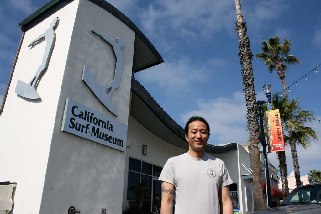 Sam Zuegner, California Surf Musuem operations manager, stands in front of the museum and its iconic logo. Plans are brewing for this year's surf film festival. Photo by Promise Yee