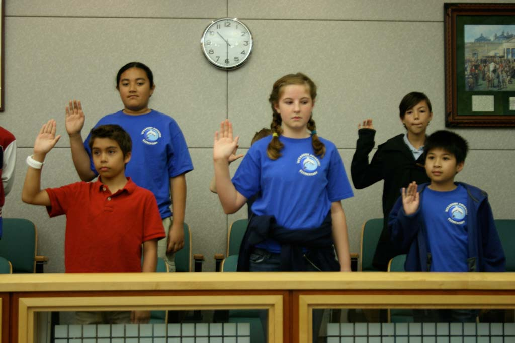 Students are sworn in as jury members as part of the mock trial. The lesson teaches students about the court process. Photo by Promise Yee