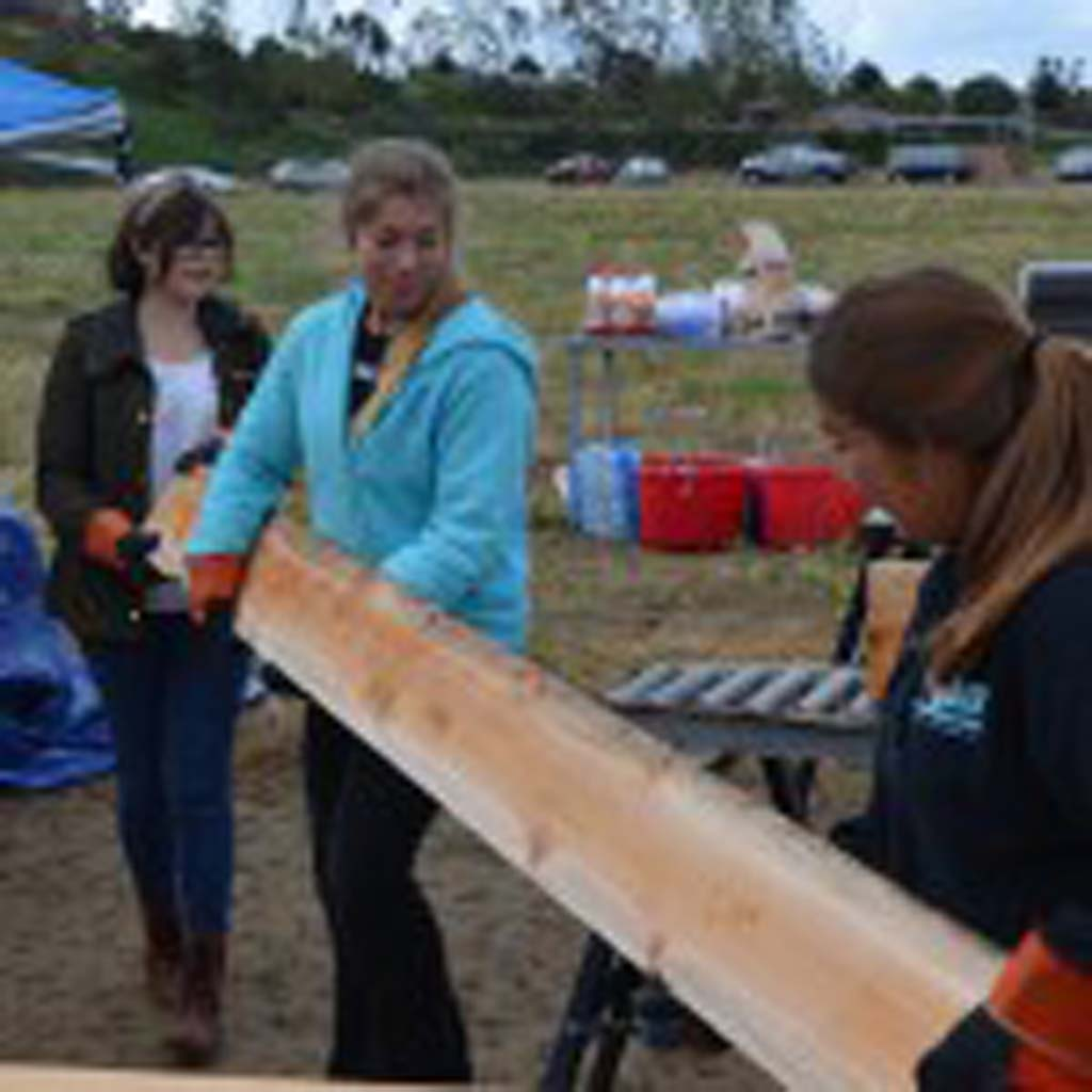 Left to right: Gabriella Garruto, Julia Ramzi and Maria Lopez move a wood slat that will make up a planter box.