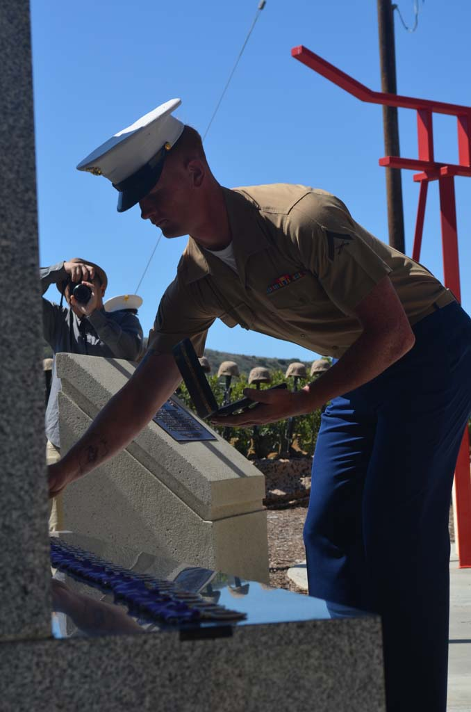 A Marine places a Purple Heart medal on the memorial wall in the San Mateo Memorial Garden on Camp Pendleton for members of the Second Battalion, 4th Marines that were killed in the Battle of Ramadi. Photo by Tony Cagala