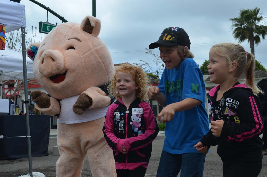 From left: Porkchop, Reese Hilliard, Brady Hilliard and Riley Hilliard do some dancing in the streets in Encinitas. Porkchop will be part of the San Diego County Fair (Del Mar Fairgrounds) Big Bite Baconfest July 5. Photo by Tony Cagala