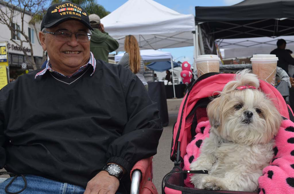Tony Banzuelo sits with Daisy Mae, a Shih Tzu AKC Canine Good Citizen and pet therapy dog with Therapy Dogs International (TDI). Photo by Tony Cagala