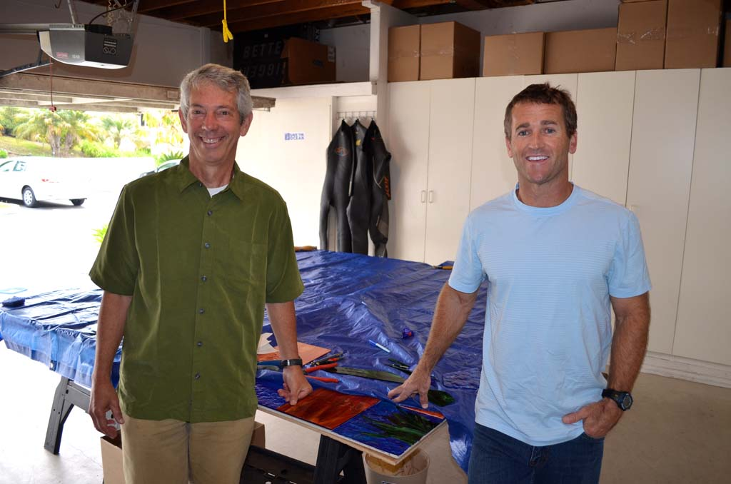 Surfing Madonna artist Mark Patterson, left, and Bob Nichols, operations director of the nonprofit Surfing Madonna Oceans Project, pose in front of a sequel to the Surfing Madonna. The tarp will be taken off this fall, revealing the new mosaic. Photo by Jared Whitlock