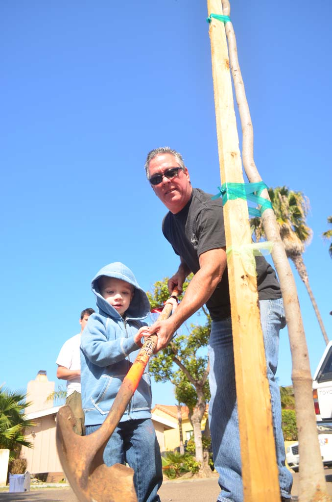 Dennis Philbin, right, with grandson Kayden Philbin work together to plant a tree. Photo by Tony Cagala
