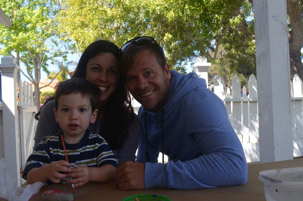 Parents Mary and Beau Moffatt with their son Elijah at the rock painting station. Photo by Tony Cagala
