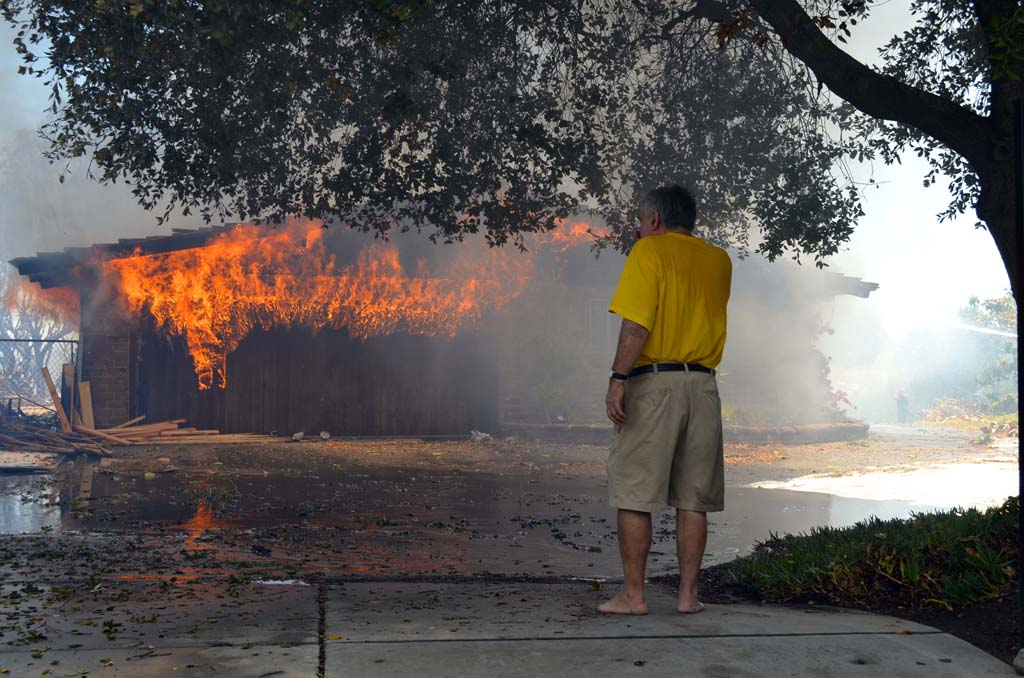 Greg Saska watches his home burn on Skimmer Court on Tuesday. Photo by Jared Whitlock