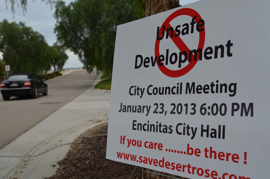 "A sign last year advocates against the ""Desert Rose"" development in Olivenhain. A Superior Court judge recently ruled the project developer must complete an environmental impact report. Doing so would shrink the project's footprint, those opposed to the project believe. File photo by Jared Whitlock"