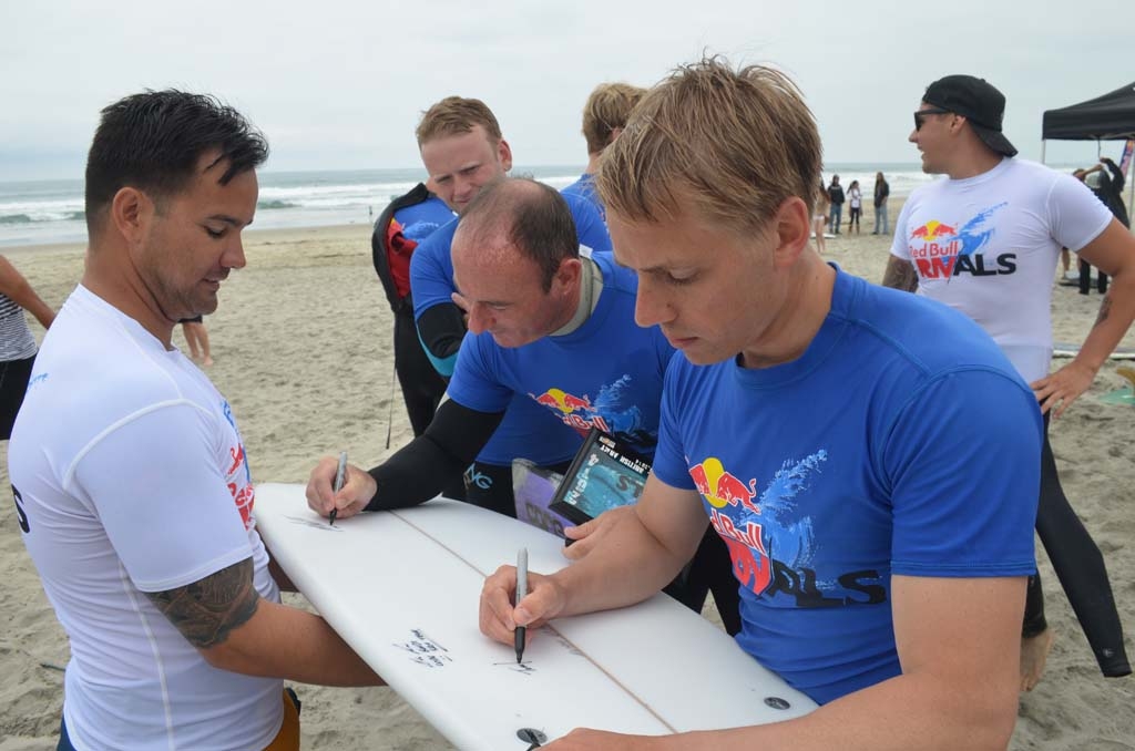 Capt. Tom Harrison, right, of the British Army surf team signs the surfboard of U.S. Military surf team member Coast Guard Petty Officer Third Class Kuilee Murphy, left. Photo by Tony Cagala