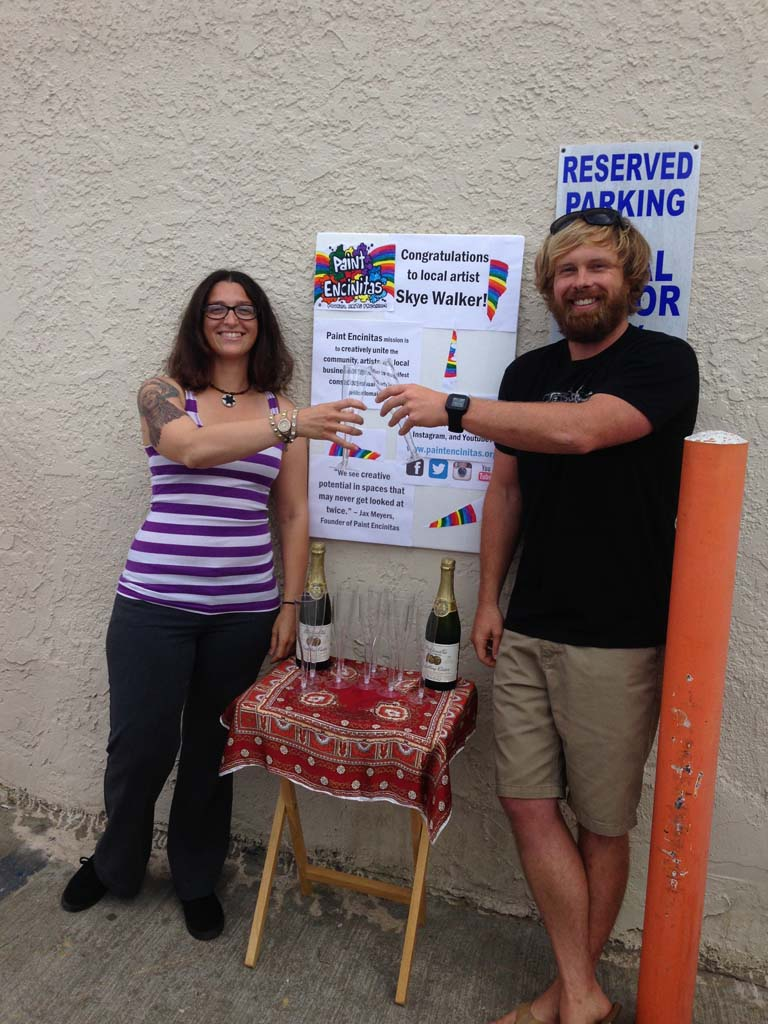 Jax Meyers, left, and artist Skye Walker clink celebratory glasses in front of Royal Liquor Store where Walker will be painting a mural this summer. Walker was selected among a host of applicants to paint this Leucadia wall. Photo by Yeshe Salz