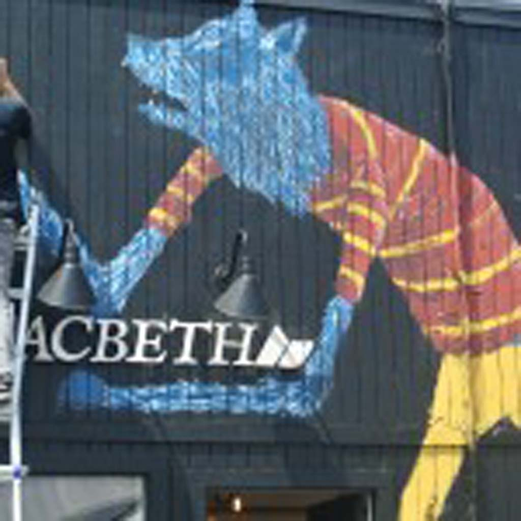 "Riverside artist Geoff Gouveia, whose signs his work as ""Wend,"" paints a mural for Macbeth Clothing Store in Encinitas. Photo by Yeshe Salz"