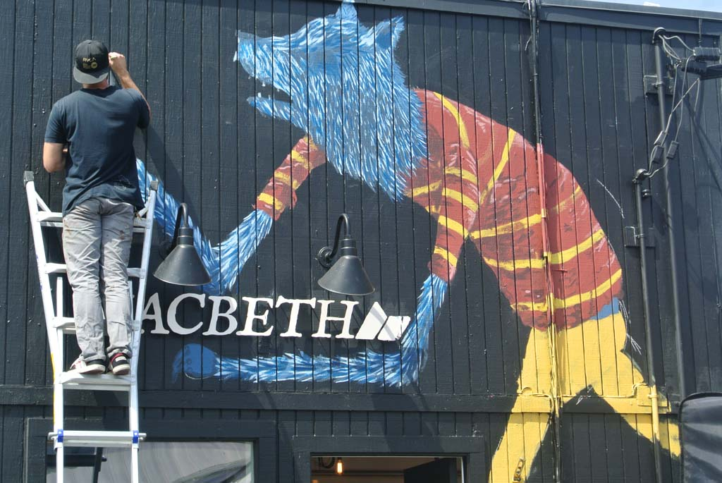 """Riverside artist Geoff Gouveia, whose signs his work as """"Wend,"""" paints a mural for Macbeth Clothing Store in Encinitas. Photo by Yeshe Salz"""