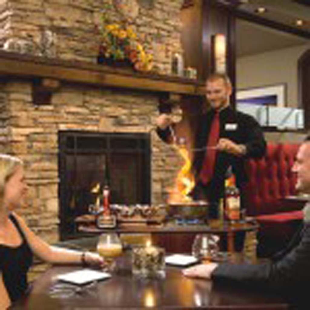 "A server at the Embers Restaurant at the Tenaya Lodge prepares flaming Bananas Diablo, so named because the cloves that punctuate the spiraling, flaming orange peel glow red ""like the devil's eyes.""  The dessert is a concoction that includes bananas, ice cream, Grand Marnier, rum and other liqueurs. (Courtesy photo)"