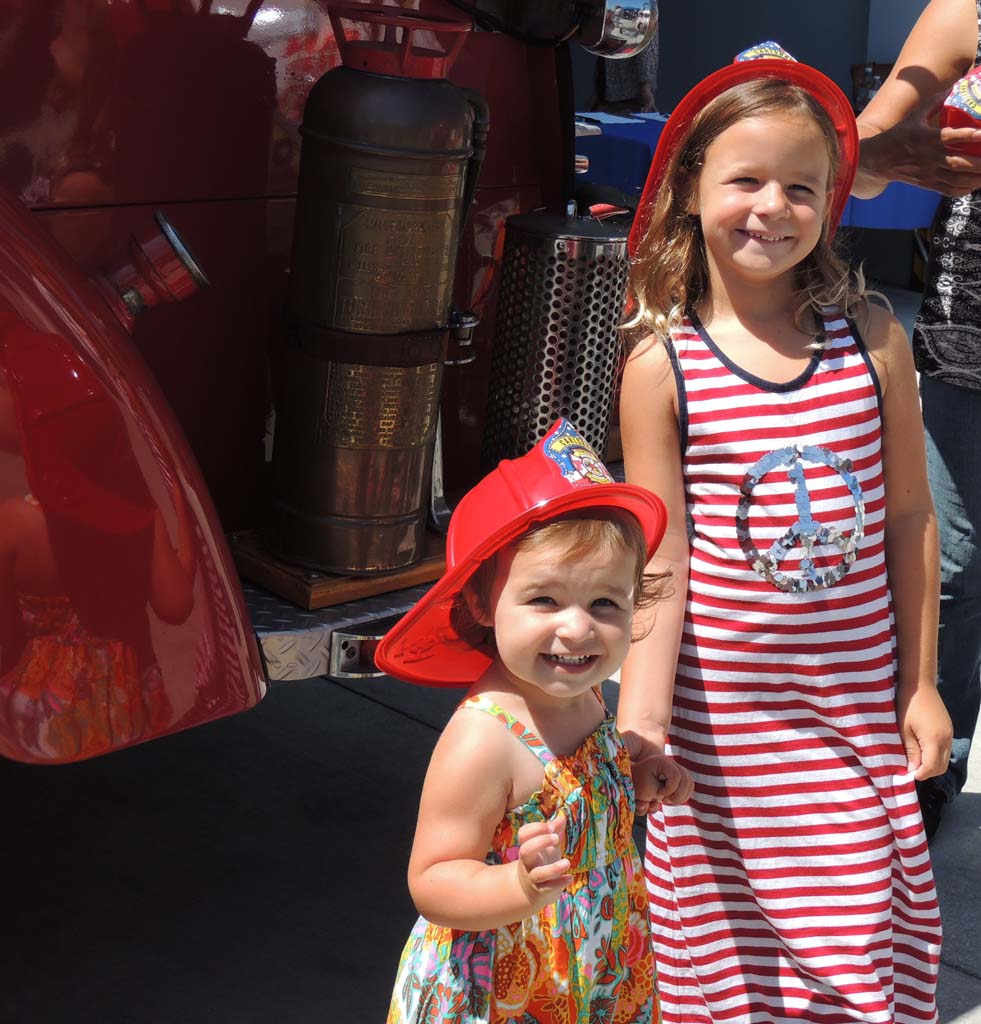 Sisters Harper Girard, 2, and Ryanne Girard, 6, pose for their mother in front of an old-fashioned fire engine at Carlsbad's Community Appreciation Day. Photo by Rachel Stine