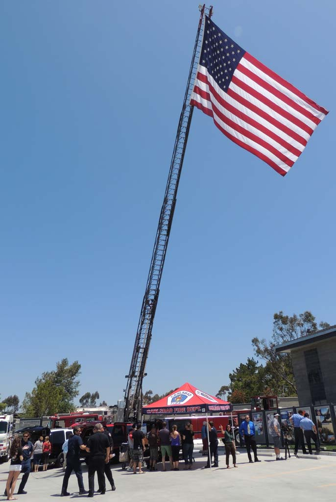 A large American flag waves in the wind from one of the fire engine ladders. Photo by Rachel Stine