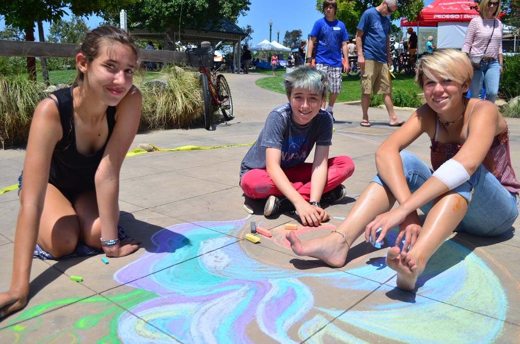 From left, Colleen McGrath, Veronica Ness and Sydney Busic draw designs in chalk at Cottonwood Creek Park on Sunday. Photo by Tony Cagala