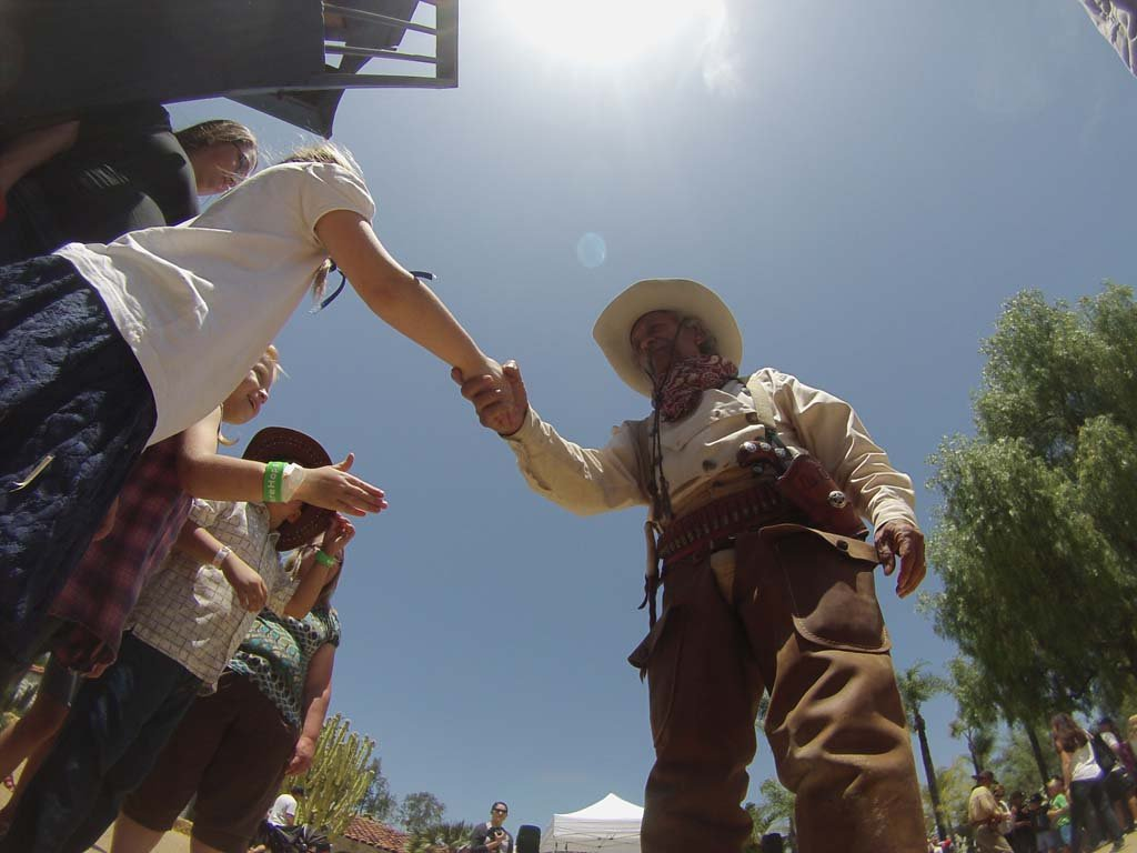 "Cowboy ""Curly Dan"" shakes the hands of kids during the Wild West Days. Photo by Tony Cagala"
