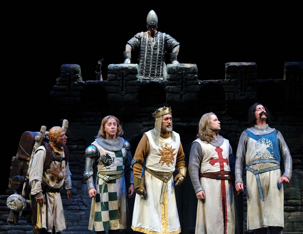 Sean Murray as King Arthur, center with crown, and the rest of the Knights of the Roundtable argue over how to defeat the taunting French castle guard. Photo by Ken Jacques Photography