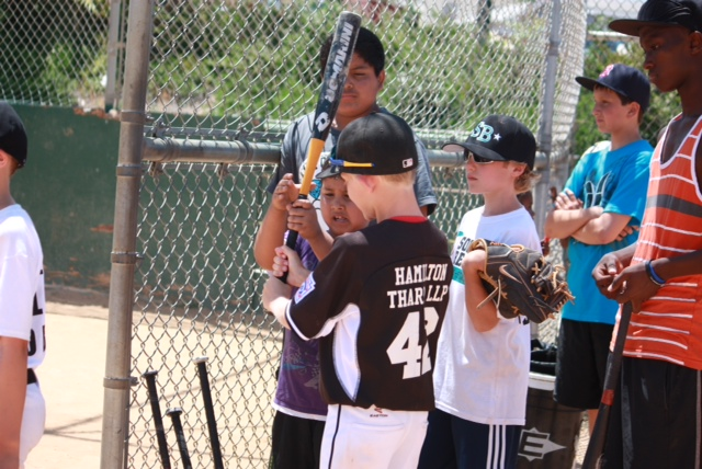 Ian King shows a youngster how to hold the bat during a recent clinic in which members of the Solana Beach Little League all-star teams, aged 9 through 11, taught a group of immigrant youngsters, mostly from Africa, how to play baseball. Courtesy photo