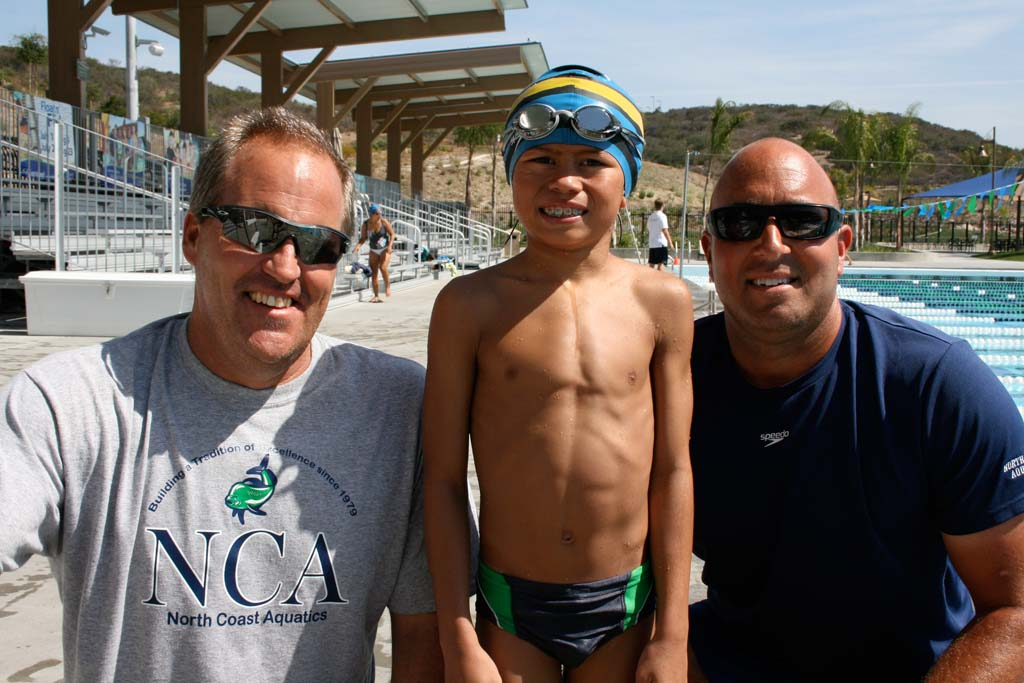 Coach Rob Mackle, swimmer Jaeden Tran, and Coach Mickey Murad take a moment after practice to talk about the upcoming Junior Olympics. Jaeden has qualified for three races. Photo by Promise Yee