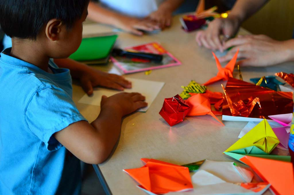 Volunteer Masayo Reed helps out with origami instruction, part of the traditional crafts at the Japan Festival at the Encinitas Library Aug. 2. Photo by Luki