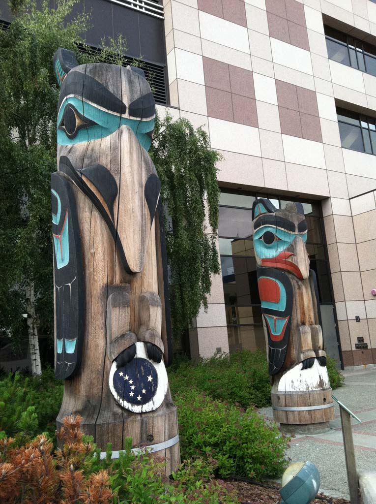 """These totems stand in front of the Nesbett Courthouse in downtown Anchorage. Artists Lee Wallace and Edwin Dewitt created """"Raven Stealing Moon and Stars"""" (left) and """"Eagle and Giant Clam."""" The eagle plays a leadership role in native mythology, while the raven is frequently portrayed as a culture hero, trickster or both. [Photo by E'Louise Ondash]"""