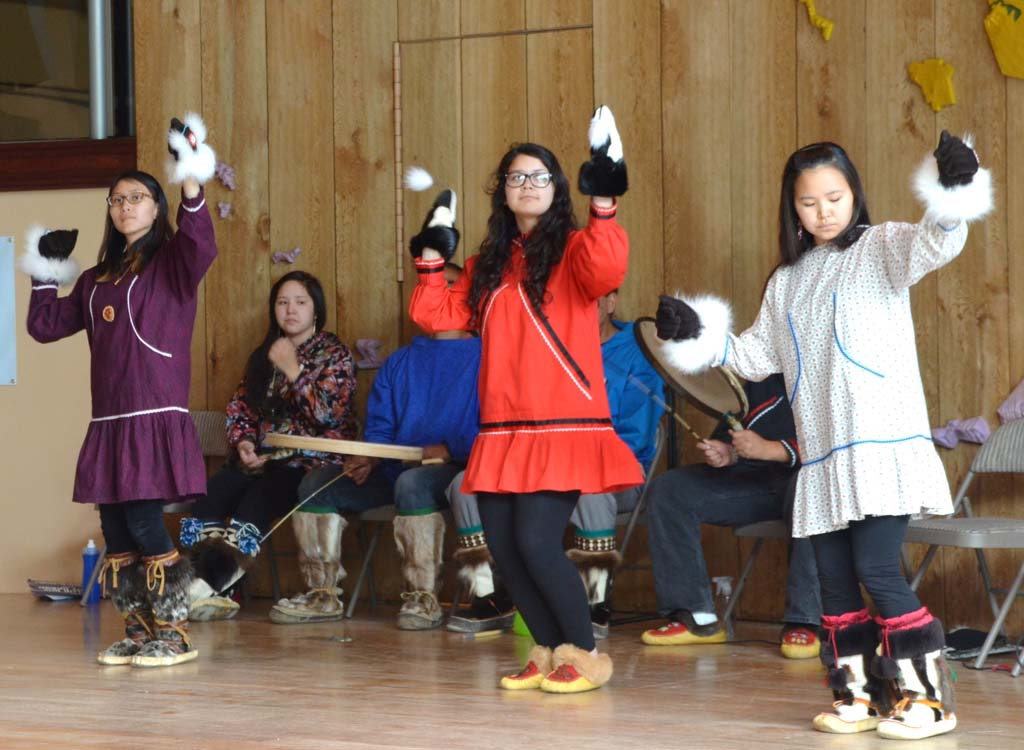 Teen members with ancestral roots in Native Alaskan villages entertain visitors with dances and songs that tell of 10,000 years of native peoples' history. The Alaska Native Heritage Center in Anchorage also offers guided walking tours of recreated native village dwellings and exhibits featuring examples of clothing, tools and artwork that illustrate how native peoples survive in Alaska's harsh environments.  [Photo by Jerry Ondash]