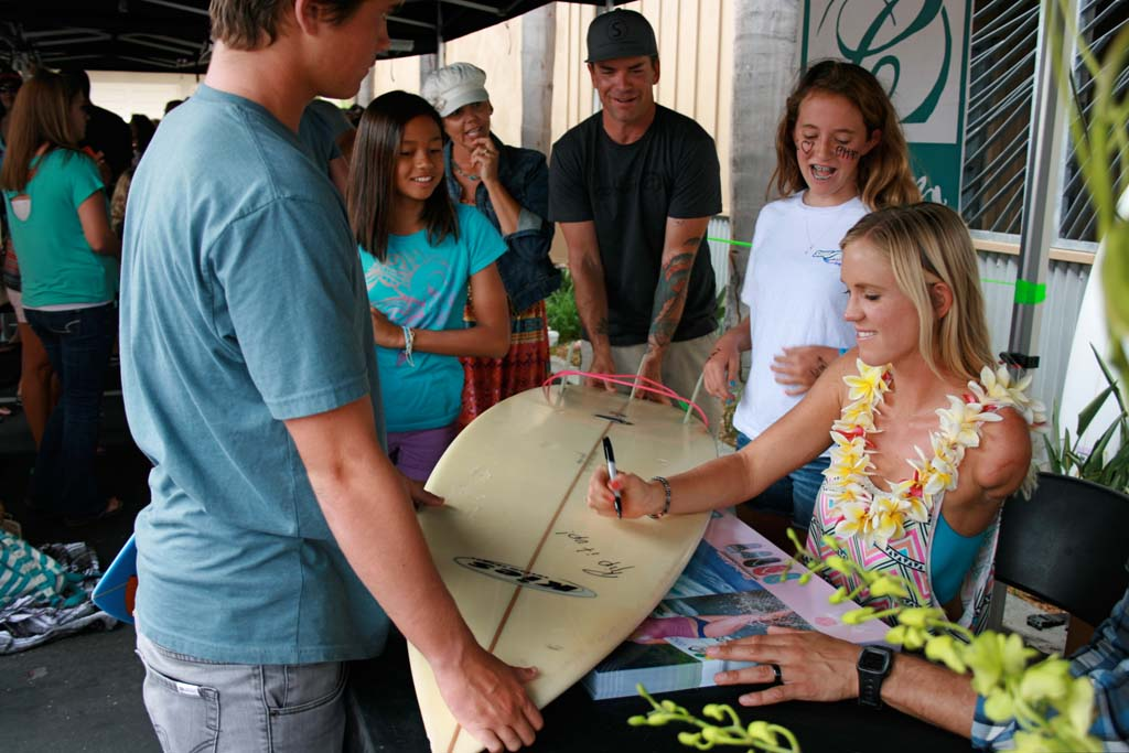Isabella Darisay, 12, of Carlsbad, left, and Chloe Pierson, 12, of Oceanside stand by as Bethany Hamilton signs Chloe's surfboard. Fans lined up around the block to meet Hamilton on July 19. Photo by Promise Yee