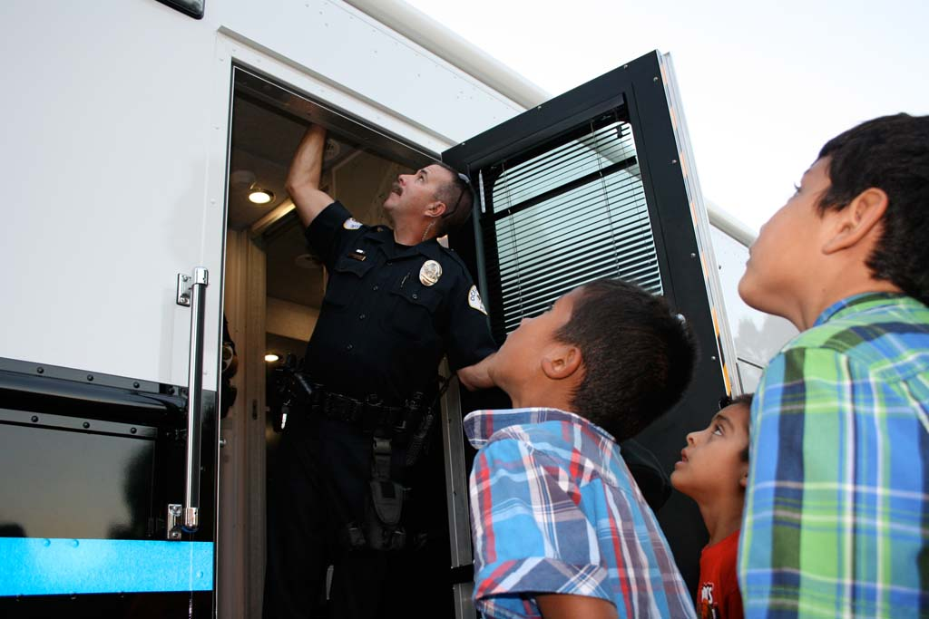 Children watch as Officer Robert Sarracino adjusts the rooftop camera on the police mobile command center. Then they follow him inside for a tour of the mobile station. Photo by Promise Yee