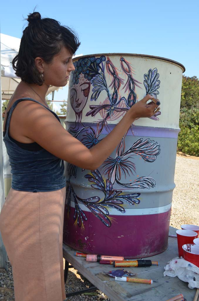 Gracen Bookmyer, on a bike tour from Oregon to California, stops by Rhino Art Co. to paint a barrel. Photo by Tony Cagala